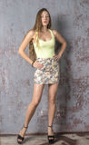 Young long-haired long-legged skinny girl in a top mini skirt and platform sandals Royalty Free Stock Photo