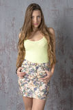 Young long-haired long-legged skinny girl in a top mini skirt and platform sandals Royalty Free Stock Photos