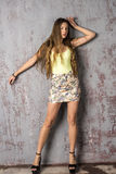 Young long-haired long-legged skinny girl in a top mini skirt and platform sandals Royalty Free Stock Image