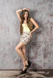 Young long-haired long-legged skinny girl in a top mini skirt and platform sandals Royalty Free Stock Images