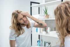 Young long haired man checking skin on face in bathroom Stock Photography