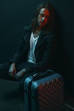 Young long haired man crouching and looking at suitcase Royalty Free Stock Image