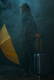 Young long haired man holding yellow umbrella and suitcase. Back view of young long haired man holding yellow umbrella and suitcase Stock Photography