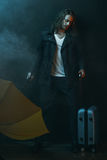 Young long haired man holding yellow umbrella and suitcase. Pensive young long haired man holding yellow umbrella and suitcase Stock Images