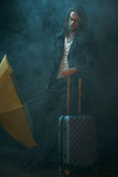 Young long haired man holding yellow umbrella and suitcase. Pensive young long haired man holding yellow umbrella and suitcase Royalty Free Stock Images