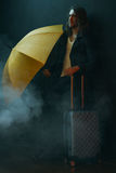 Young long haired man holding yellow umbrella and suitcase. Pensive young long haired man holding yellow umbrella and suitcase Royalty Free Stock Photography