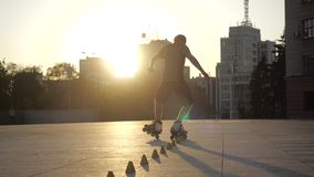 Young long-haired man is professionally skating between cones on a nice evening sunset in a city park. Freestyle slalom. Young man slalom skater is dancing stock footage
