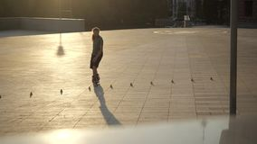 Young long-haired man roller skater is dancing between cones in the evening in a city park at sunset. Freestyle slalom. Young man slalom skater is dancing stock footage