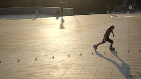 Young long-haired man roller skater is dancing between cones in the evening in a city park at sunset. Freestyle slalom. Young man slalom skater is dancing stock video