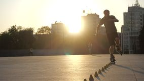Young long-haired man roller skater is dancing between cones in the evening in a city square at sunset. Freestyle slalom. Young man slalom skater is dancing stock video