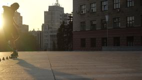 Young long-haired man is skating between cones on a nice evening in a city park. Freestyle slalom Roller skating between. Young man slalom skater is dancing stock footage