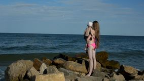 Young long-haired woman holding a child standing on the beach and shows the distance. Back view.  stock footage