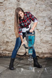 Young long-haired woman with a jackhammer Royalty Free Stock Photos