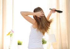 Young long haired woman wake up early morning Stock Photo
