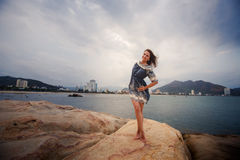 young long-legged girl barefoot stands tiptoe against sea Royalty Free Stock Photo