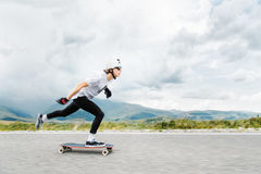The young Longboarder pushes his foot out on his longboard over the country road stock photos