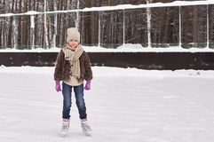 Young longhair girl wearing in casual winter clothing on ice rink stock photography