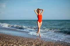 Young longhaired girl in red swimsuit stock images