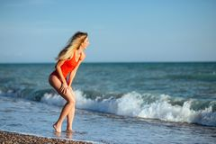 Young longhaired girl in red swimsuit royalty free stock photography