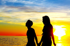Young Love. A young couple shillouted walking in Newport Beach Stock Photo