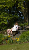 Young Love. Two young people huddling on bench in intimate conversation stock photo