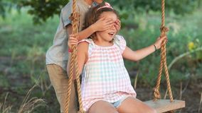 Young love between boy and girl on romantic summer evening. Couple of happy kids hugging and swinging on wooden swing at stock video footage