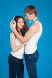 Young love couple. Boy putting on headphones, listening music in Royalty Free Stock Image