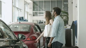 Young in love couple choose the automobile in car showroom. In love couple is choosing the automobile in car dealership. Young girl ask her boyfriend to buy a stock footage