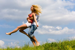 Young love couple having fun on spring meadow. Against the backdrop of blue sky Royalty Free Stock Photo