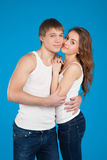 Young love couple  holding each other in the studio over blue ba Stock Photos