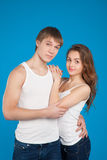 Young love couple holding each other in the studio. Over blue background Royalty Free Stock Images