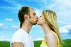 Young love couple kiss in field. Under blue sky Royalty Free Stock Photo