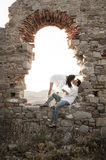 Young in love couple kissing inside brick archway of old building. Young in love couple sitting inside brick archway of old building ruin Stock Photo