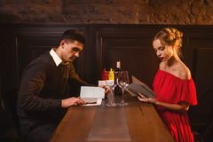 Young love couple look at the menu in restaurant Royalty Free Stock Photography