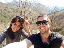 Young love couple in the mountain. Young friends smiling and making selfie in the mountain stock photos