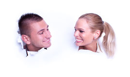 Young love couple peer through the wallpaper Royalty Free Stock Images