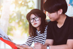 Young love couple reading a book together in the cafe stock photography