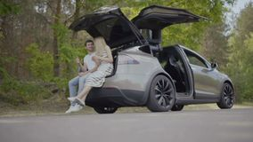 Young in love couple sit inside the trunk of the electric car and talking. Happy in love couple sit inside th trunk of the car and talking. Young girl and guy stock video
