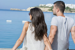 Young love  couple sitting on the beach looking the sea. Happy young couple on summer vacation enjoying the sea view Stock Photo