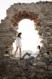 Young in love couple sitting inside brick archway of old building. Ruin Royalty Free Stock Image