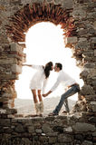 Young in love couple sitting inside brick archway of old building ruin. At sundown Stock Photography