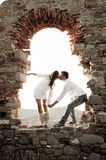 Young in love couple sitting inside brick archway of old building ruin. At sundown Royalty Free Stock Images