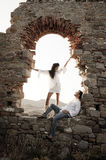Young in love couple sitting inside brick archway of old building ruin. At sundown Stock Photos