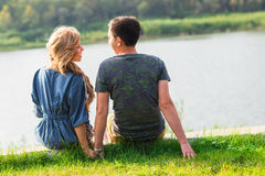 Young love couple sitting on the river bank in summer Stock Photos