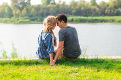 Young love couple sitting on the river bank in summer.  Royalty Free Stock Photo