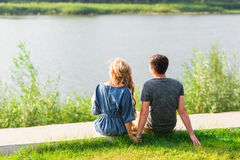 Young love couple sitting on the river bank in summer.  Royalty Free Stock Images