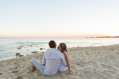 Young love couple sitting together on beach, rear view Royalty Free Stock Photo