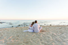 Young love couple sitting together on beach, rear view Stock Photos