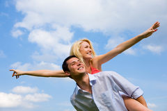 Young love Couple smiling under blue sky. Girl on top. Pulls hands up Stock Image