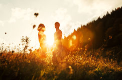 Young in love couple stay on meadow in bright sunset light Stock Photography